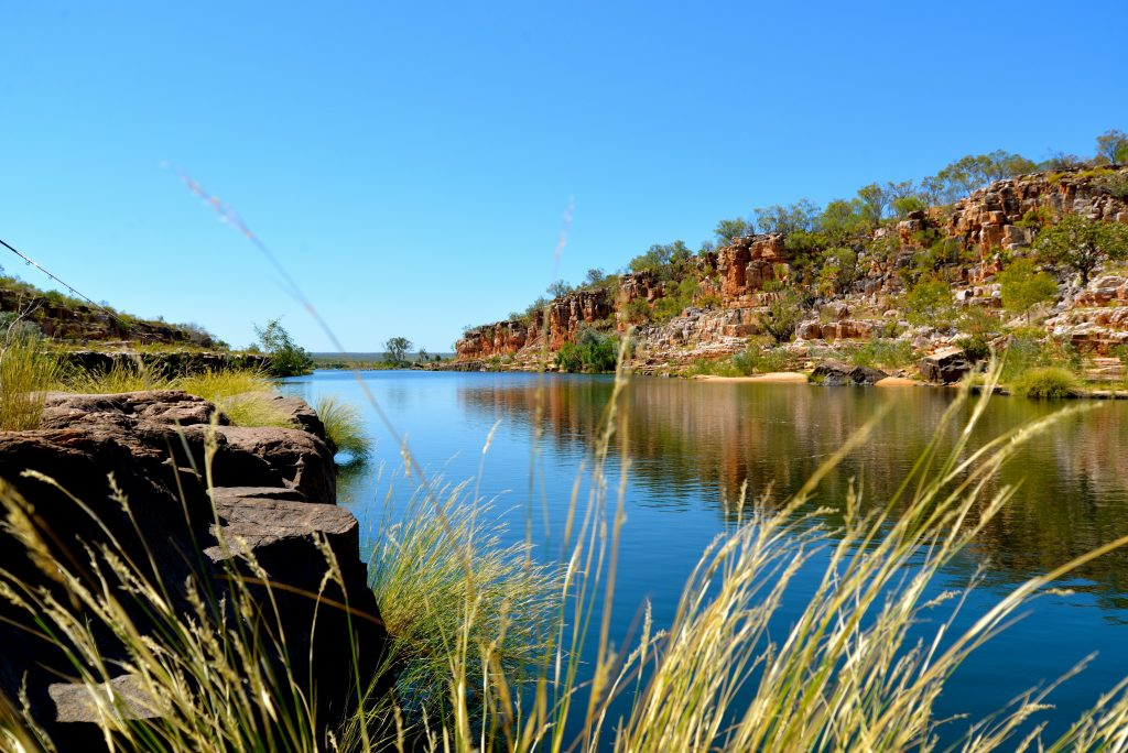 Stunning blue water in The Kimberley, red rock gorged on one side black rock and lush grasses